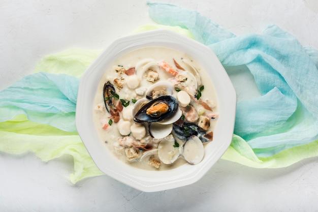Zuppa di molluschi e latte in un piatto bianco. gli ingredienti principali sono crostacei, brodo, burro, patate e cipolle.