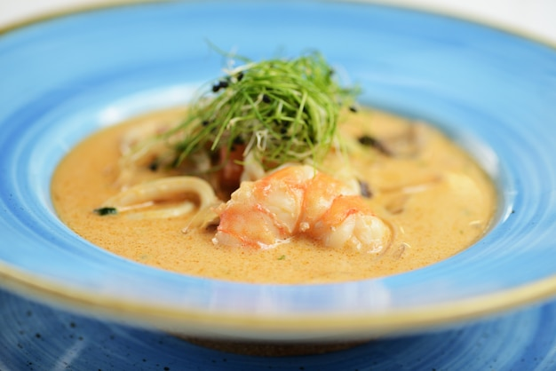 Zuppa di noodles di pesce piccante con gamberi e funghi