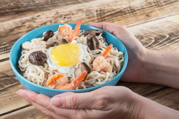 Zuppa di noodles istantanei con gamberi, uova e funghi.