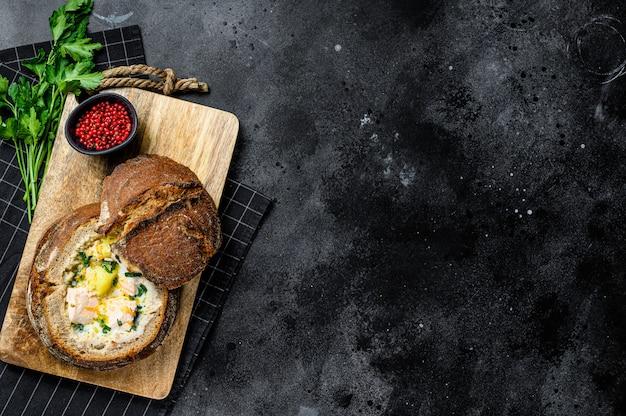 Zuppa di pesce cremosa finlandese con salmone, trota, patate servite nel pane. sfondo nero, vista dall'alto, spazio per il testo