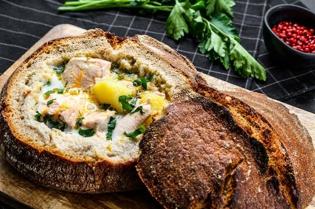 Zuppa di pesce cremosa finlandese con salmone, trota, patate servite nel pane. sfondo nero, vista dall'alto.