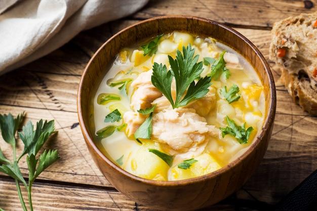Zuppa di pesce in una ciotola di legno con erbe fresche.