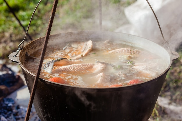 Zuppa di pesce preparata in una pentola sopra un fuoco aperto, all'aperto