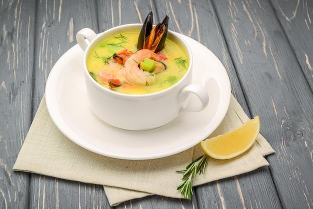 Zuppa di pesce, su un tavolo di legno, con gamberi