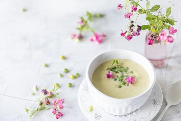 Zuppa di piselli verde su un tavolo di marmo bianco
