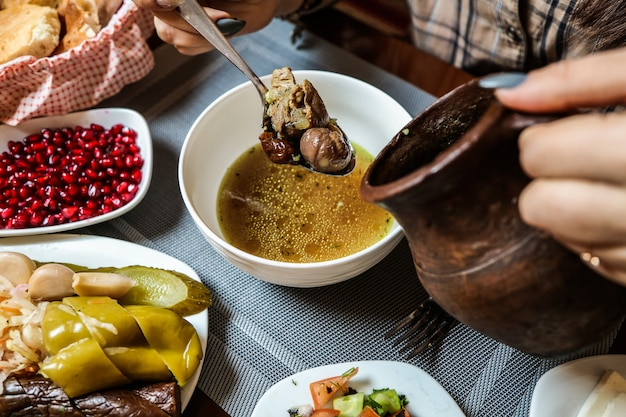 Zuppa di piti tradizionale con carne di agnello e verdure e vista dall'alto di snack laterali