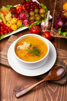 Zuppa di pollo con un pezzo di carne in salsa di pomodoro. prezzemolo tritato, in una ciotola bianca decorata con turshu sul tavolo di legno.