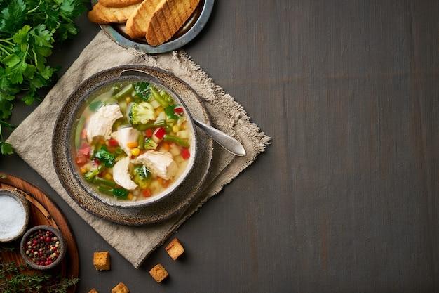 Zuppa di pollo fatta in casa con verdure, broccoli su un marrone scuro