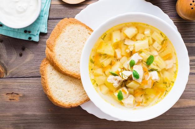 Zuppa di pollo pronta da mangiare con patate ed erbe in una ciotola bianca su un tavolo di legno. vista dall'alto
