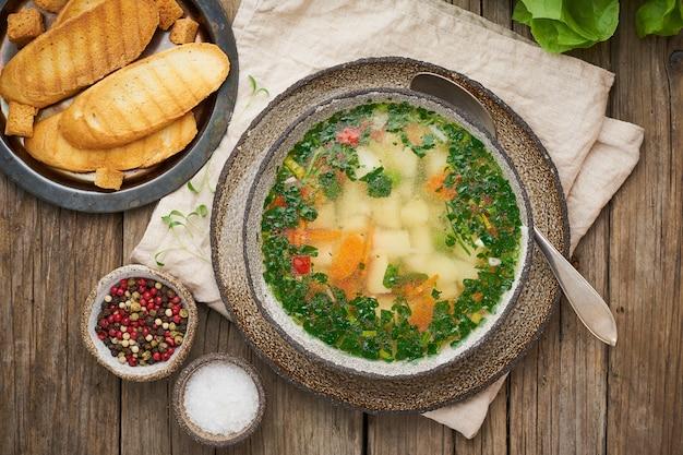 Zuppa di pollo rustico con contorno, prezzemolo, verdure, piatto fatto in casa sul vecchio tavolo scuro, vista dall'alto