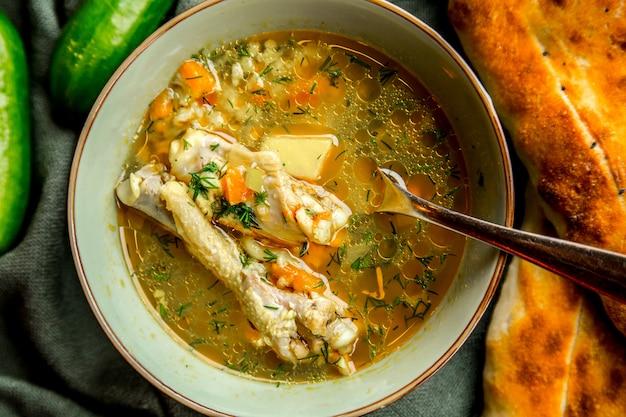Zuppa di pollo vista dall'alto servita con pane e cetrioli alle erbe
