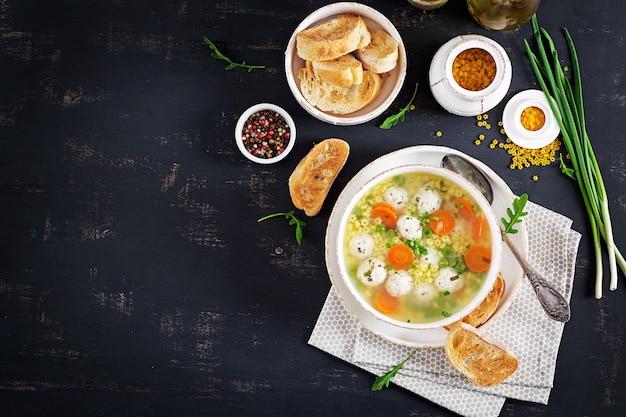 Zuppa di polpette italiane e pasta stellare in ciotola sul tavolo nero.