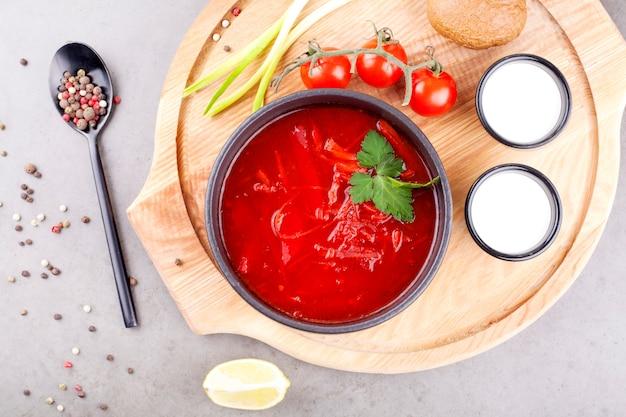 Zuppa di pomodoro con, decorato con prezzemolo, in un piatto nero, su una tavola di legno, decorato con pomodori e cipolle. minestre di concetto o cibo sano.