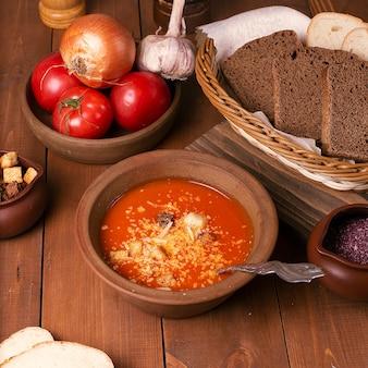 Zuppa di pomodoro con scaglie di parmigiano e pane nero.