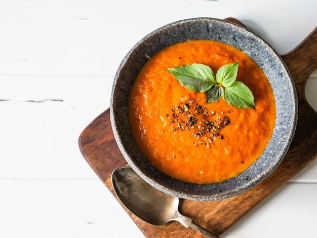 Zuppa di pomodoro con spezie e basilico fresco su un fondo di legno bianco.