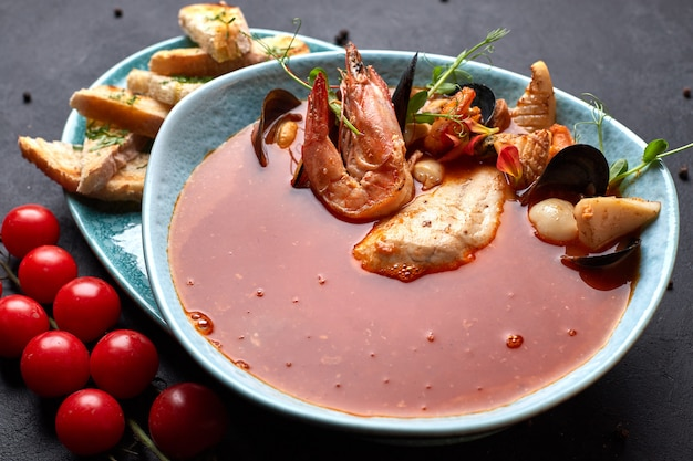 Zuppa di pomodoro e frutti di mare, su uno sfondo scuro, bouillabaisse