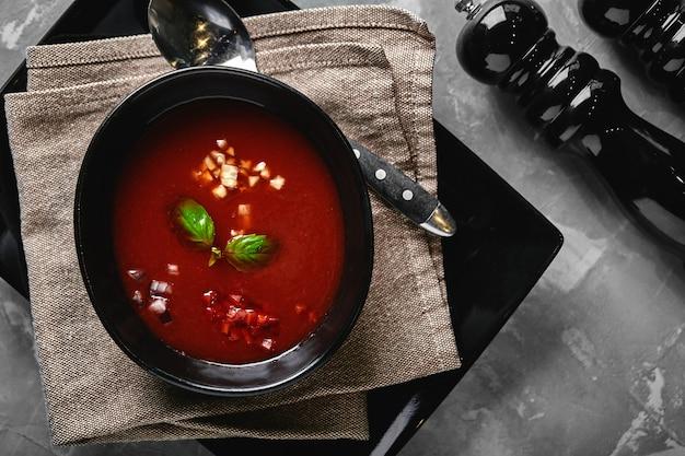 Zuppa di pomodoro in una ciotola nera su uno spazio di pietra grigia.