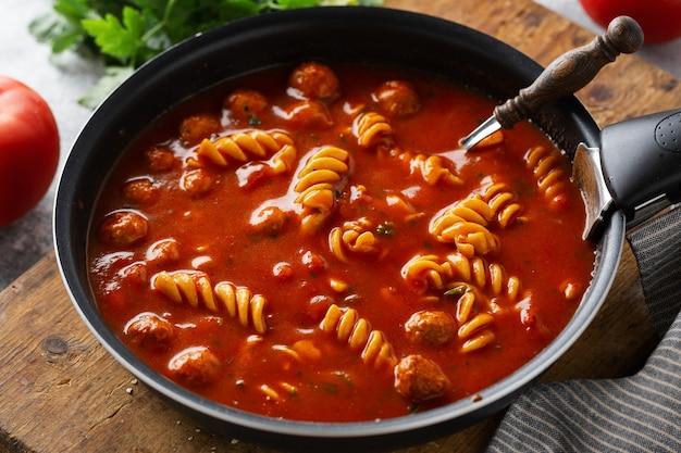 Zuppa di pomodoro italiana con pasta di tagliatelle e polpette cotte in padella. avvicinamento