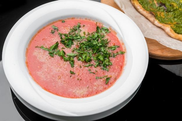 Zuppa di pomodoro, peperoncino, salsa con olio d'oliva, rosmarino e paprika affumicata su un fondo di legno.