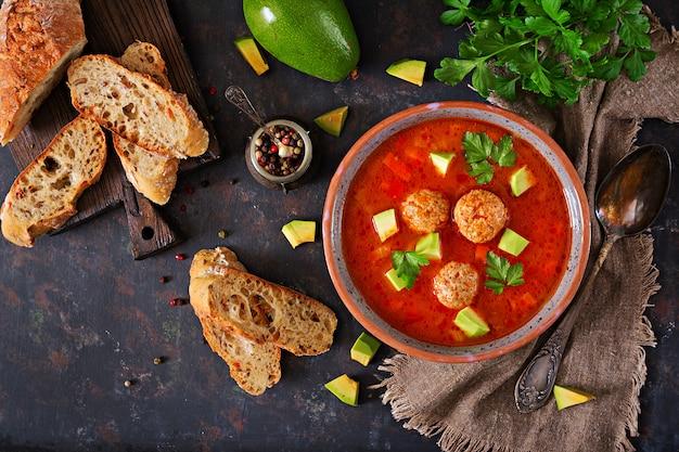 Zuppa di pomodoro piccante con polpette e verdure. servito con avocado e prezzemolo. cena sana. piatto disteso. vista dall'alto