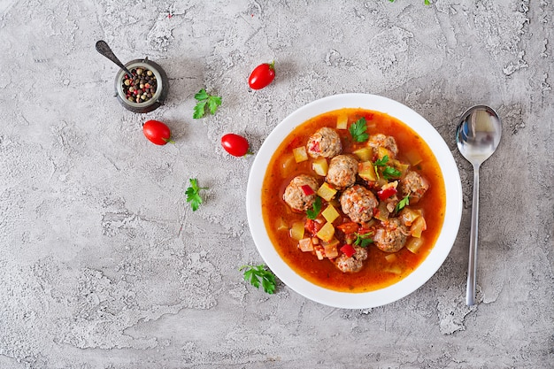 Zuppa di pomodoro stufato caldo con polpette di carne e verdure alzato in una ciotola sul tavolo. zuppa di albondigas