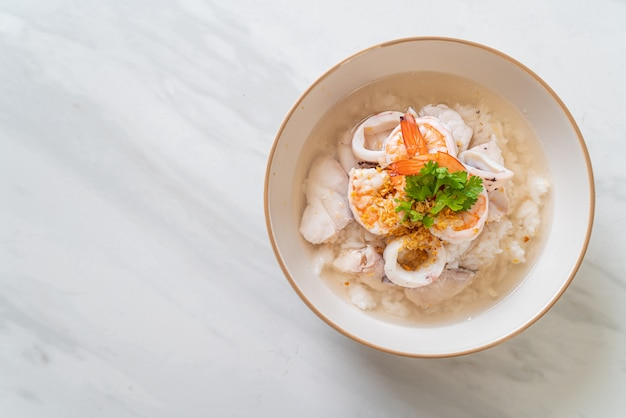 Zuppa di porridge o riso bollito con scodella di pesce (gamberi, calamari e pesce)