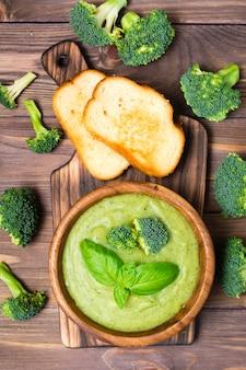 Zuppa di purea di broccoli calda fresca pronta da mangiare con fette di broccoli e foglie di basilico in un piatto di legno e fette di pane bianco tostato su un tagliere e infiorescenze di broccoli
