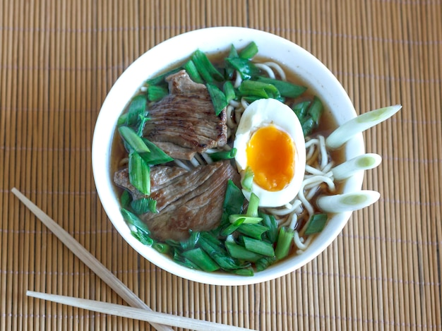 Zuppa di ramen con cipolle fresche, uova sode e carne fritta