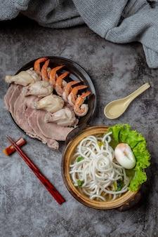 Zuppa di stile asiatico con noodles, carne di maiale e cipolle verdi da vicino in una ciotola sul tavolo.