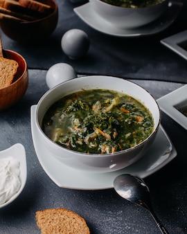 Zuppa di verdure calda con verdure bollite all'interno del piatto bianco rotondo con pane pagnotte uova sul tavolo grigio