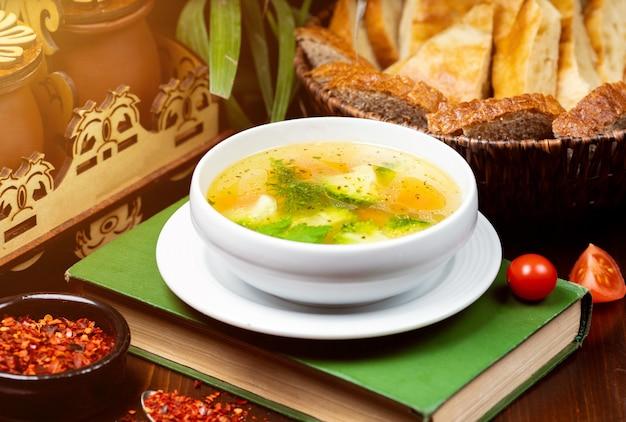 Zuppa di verdure di pollo fatta in casa, vista dall'alto su un libro sul tavolo