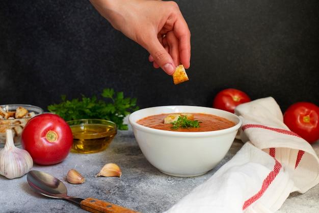 Zuppa di verdure fredda estiva tradizionale gazpacho. pomodori, aglio, basilico, olio d'oliva. crostino della tenuta della mano della donna. cucina mediterranea, spagnola. vista frontale. sfondo nero. copia spazio