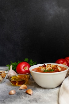 Zuppa di verdure fredda estiva tradizionale gazpacho. pomodori, aglio, basilico, prezzemolo, olio d'oliva e crostini. cucina mediterranea, spagnola. avvicinamento. sfondo nero. copia spazio. verticale