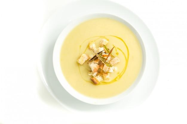 Zuppa di verdure gialla in un piatto bianco dall'alto con crostini e olio d'oliva
