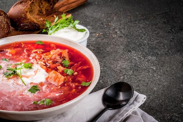 Zuppa di verdure tradizionale ucraina borscht, con crema dura. panini prezzemolo di segale, sul tavolo di pietra nera, copia spazio