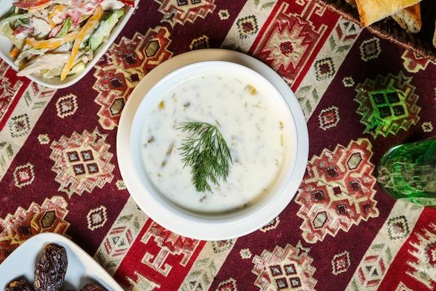 Zuppa di yogurt vista dall'alto con erbe in un piatto