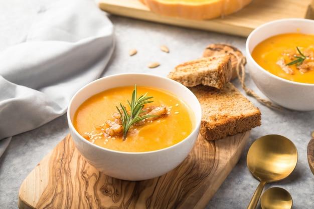 Zuppa di zucca autunnale fatta in casa alla zucca con pane e semi. vista dall'alto