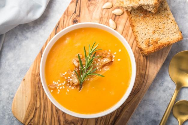Zuppa di zucca autunnale fatta in casa con zucca e pane con semi e pane. vista dall'alto