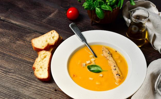 Zuppa di zucca con basilico e grissini in un piatto di porcellana bianca, ricetta di zucca