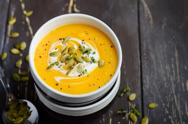 Zuppa di zucca con crema e semi di zucca sulla tavola di legno.