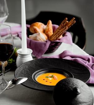 Zuppa di zucca con gamberi e un bicchiere di vino rosso