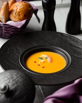 Zuppa di zucca con gamberi e un cesto di pane
