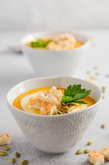 Zuppa di zucca con panna, crostini, semi di zucca e prezzemolo su uno sfondo grigio di cemento o pietra.