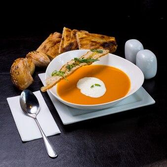 Zuppa di zucca con schiuma di latte focacce cracker rucola vista laterale