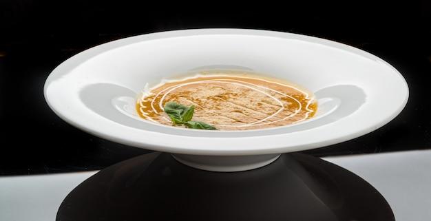 Zuppa di zucca e carota con panna e prezzemolo su superficie di legno scuro vista dall'alto