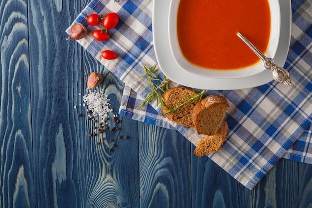Zuppa di zucca e carote con panna e prezzemolo su sfondo blu in legno vista dall'alto copia spazio