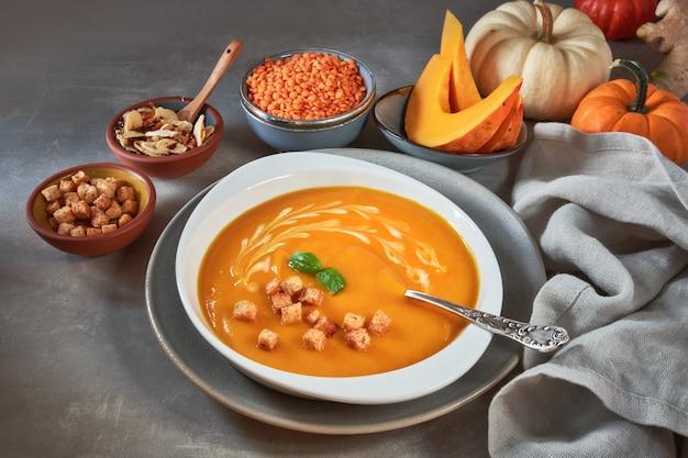 Zuppa di zucca e lenticchie rosse in ciotola di ceramica condita con basilico, panna e crostini