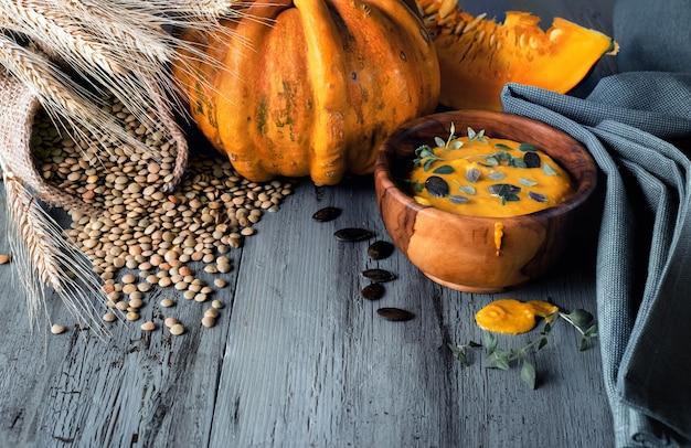 Zuppa di zucca e lenticchie servita in una ciotola di legno d'ulivo con timo