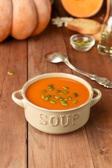Zuppa di zucca fatta in casa con semi. minestra di zucca americana tradizionale in ciotola con il cucchiaio e gli ingredienti su fondo di legno.