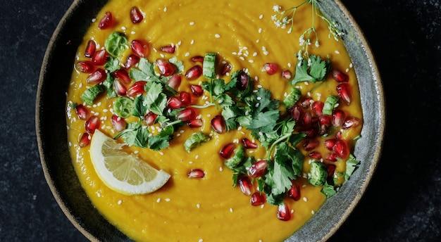 Zuppa di zucca fresca condita con semi di prezzemolo e melograno